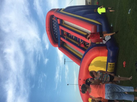 A bouncy house is being used by children at the block party. The block party took place after the parade.