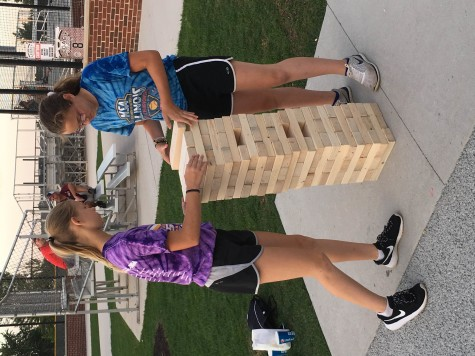 Two girls play Jenga together during the block party. The block party was held from 6:30-10 p.m.