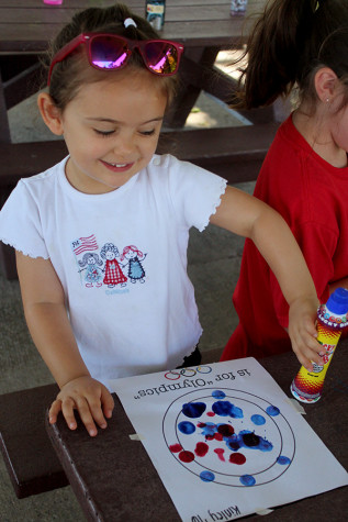 The young girl is coloring with markers at Kiddy Kamp. Kiddy Kamp was held from 10:30 a.m till 12 p.m.
