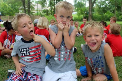 Three kids make silly faces to attempt to make the other children laugh on the last day of camp. The camp lasted seven weeks.
