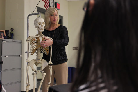 Mrs. Parks demonstrates where the jugular notch is. Students were able to touch and see the skeleton up close after the lesson was over.