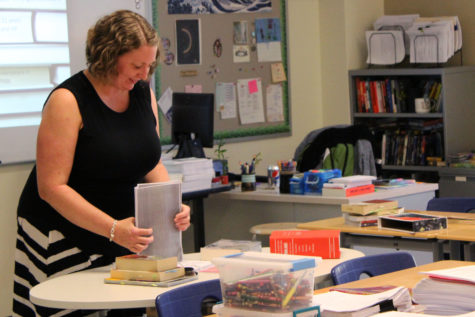 Mrs. Kathryn Clark, English, organizes a stack of handouts for parents. Her class was full of many of parents eager to learn about what their students would be covering in the course.